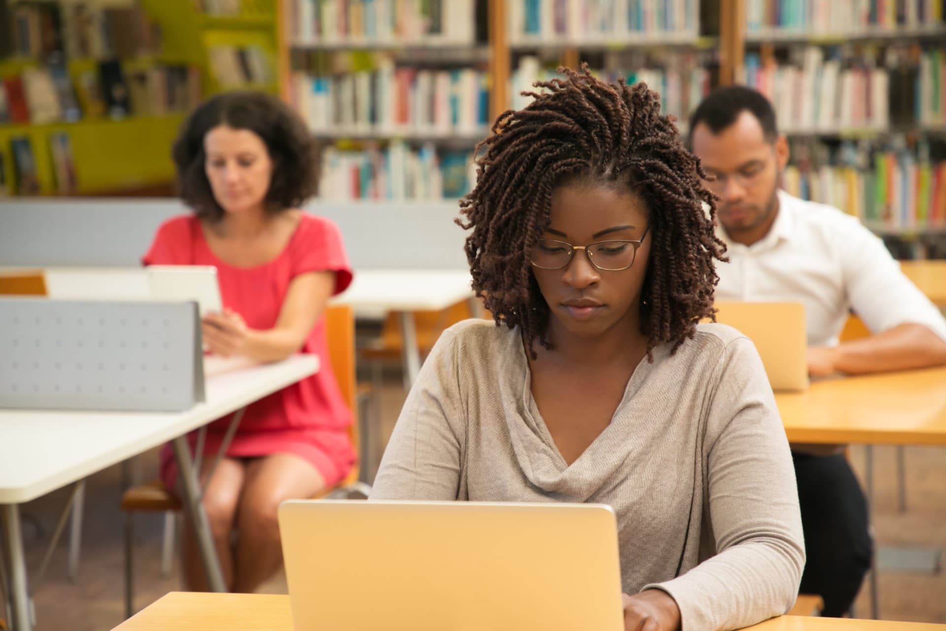 Serious African American student studying in library computer class. People sitting at desks and using laptops in classroom with bookshelves. Studying concept
